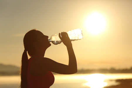 Profile of a fitness woman silhouette drinking water from a bottle at sunset with the sun in the background