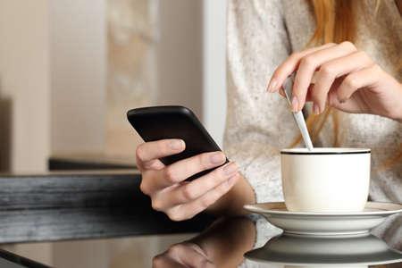 Mano de la mujer utilizando un teléfono inteligente durante el desayuno en su casa mientras se prepara una taza de café Foto de archivo