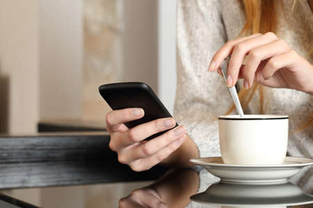 llamando: Mano de la mujer utilizando un teléfono inteligente durante el desayuno en su casa mientras se prepara una taza de café Foto de archivo