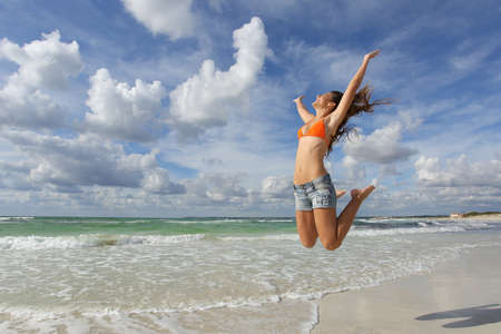 Happy girl wearing bikini jumping on the beach on holidays with a cloudy sky in the background Foto de archivo