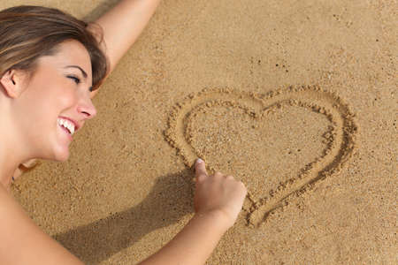 the admirer: Close up portrait of a happy woman in love drawing a heart on the sand of the beach