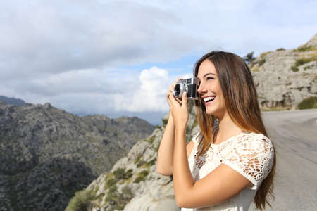photo shooting: Photographer tourist enjoying vacations and taking a photo in a mountain road