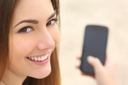 chicas comprando: Close up retrato de una mujer sonriente usando un teléfono inteligente en la playa