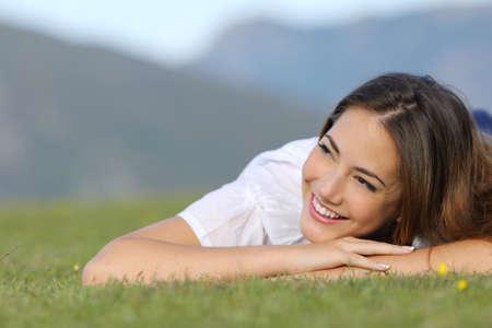 Mujer bonita feliz pensando en la hierba y que mira la cara en la montaña