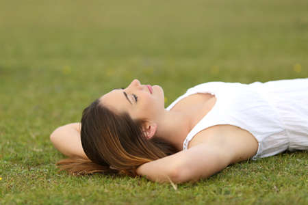 rest in peace: Relaxed woman lying on the grass sleeping in a tranquil scene with a green background