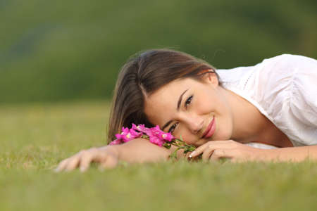 Relaxed woman resting on the green grass with flowers in a park with a green background