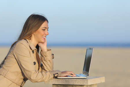 Side view of a self employed woman working with a laptop on the beach