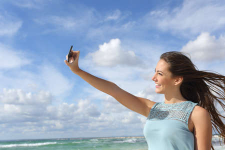 Girl photographing a selfie with a smart phone on the beach enjoying holidays in a sunny day photo