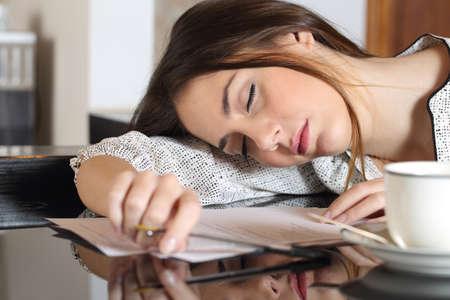 agotado: Mujer con exceso de trabajo cansado durmiendo mientras trabajaba escribiendo notas