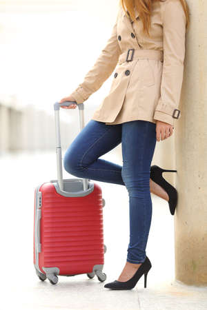 woman holding bag: Vertical view of a tourist woman legs waiting with a suitcase in an airport or station Stock Photo