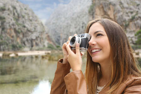 reflex: Tourist traveler woman photographing a landscape in the mountain with a slr vintage camera Stock Photo