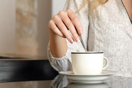 stirring: Woman hand preparing a cup of coffee at home