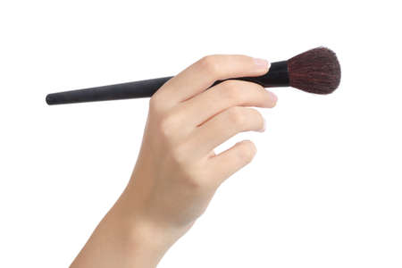 Woman hand using a makeup brush isolated on a white background photo