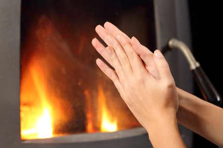 estufa: Mujer que frota las manos y calefacción delante una chimenea en casa en invierno Foto de archivo