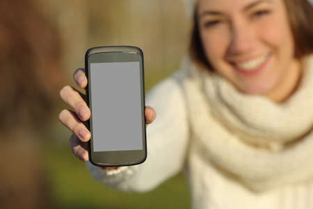 holding close: Happy woman showing a blank smart phone screen outdoors in winter