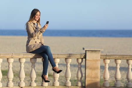 Casual woman texting in a smart phone on the beach in winter with the sea in the background
