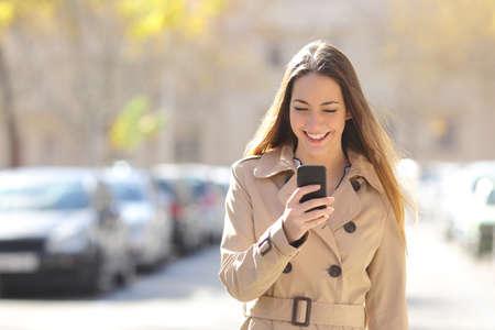 Gelukkig vrouw lopen en het gebruik van een slimme telefoon op de straat in de winter