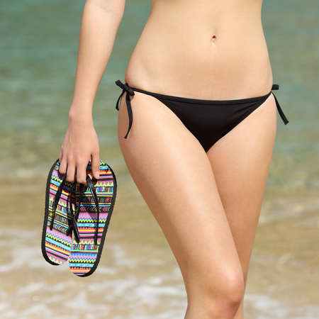 flip flops on the beach: Woman wearing bikini walking holding flip flops in her hand with the sea in the background