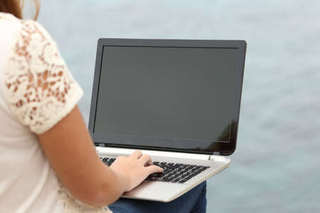 laptop outside: Woman working with a laptop and showing the display with the sea in the background