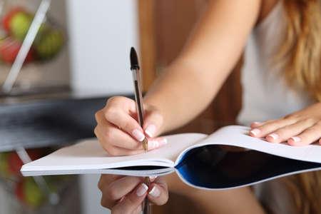 persona escribiendo: Primer plano de una mano escribiendo mujer escritora en un cuaderno en el país en la cocina
