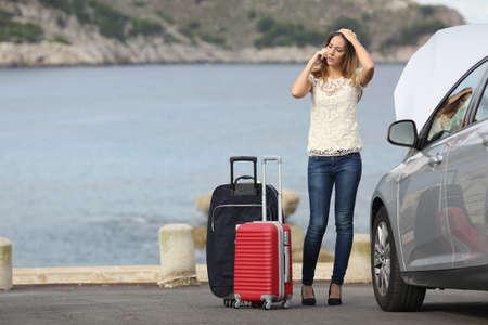 mujer con maleta: Mujer preocupante viajero llamando asistencia con un coche de la ruptura en la playa con el mar de fondo