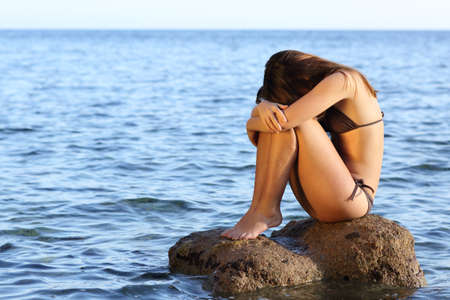 Mujer preocupada solo que se sienta en una roca en la playa en el medio del océano