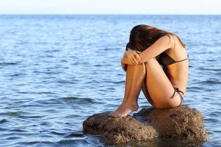 mujeres tristes: Mujer preocupada solo que se sienta en una roca en la playa en el medio del océano