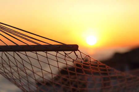 hammock: Cerca de una hamaca en la playa al atardecer con el sol en el fondo Foto de archivo