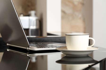 インテリアやオフィスのコーヒーのカップを持つテーブル職場のラップトップ