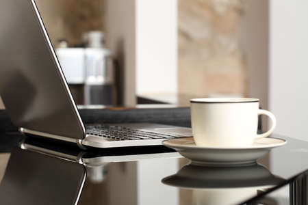 Laptop on a table workplace with a cup of coffee in a home interior or office