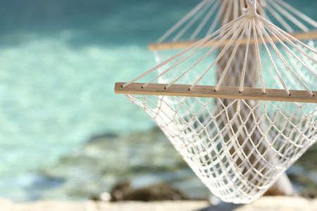 Resekoncept med en hängmatta i en tropisk strand med turkost vatten i bakgrunden
