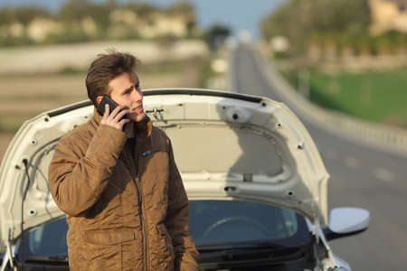roadside assistance: Angry man calling roadside assistance for his breakdown car in a road in winter Stock Photo