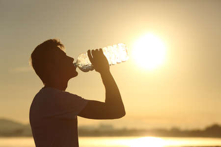 man drinking water: Profile of a fitness man silhouette drinking water from a bottle at sunset with the sun in the background