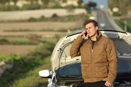 Guy calling roadside assistance for his breakdown car i a country road Stockfoto
