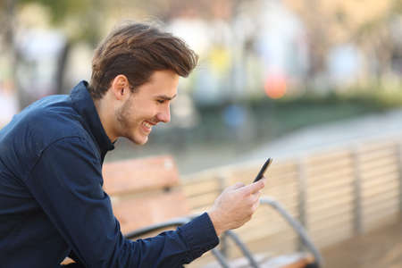 typing man: Profile of a happy guy using a smart phone sitting on a bench in a park