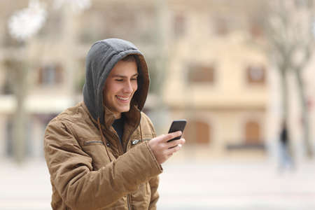 teen: Happy teen boy walking on the street and using a smart phone