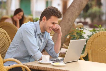 Happy man watching social media in a laptop in a restaurant terrace