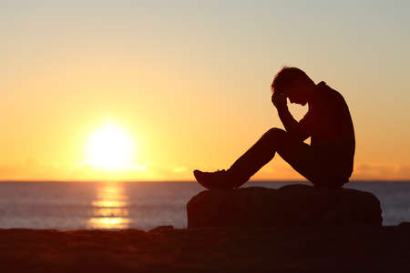 Sad man silhouette worried on the beach at sunset with the sun in the background Stock Photo