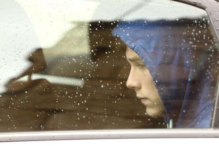 visage profil: Sad adolescent garçon inquiet intérieur d'une voiture en regardant à travers la fenêtre