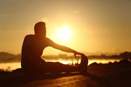 バック グラウンドで太陽が夕日ストレッチ フィットネス ランナー男のシルエット