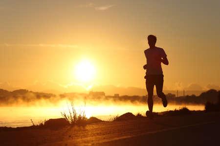 日の出の太陽がバック グラウンドで走っている人のシルエット