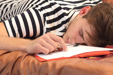 exam room: Tired student resting in the bed of his bedroom while he was working