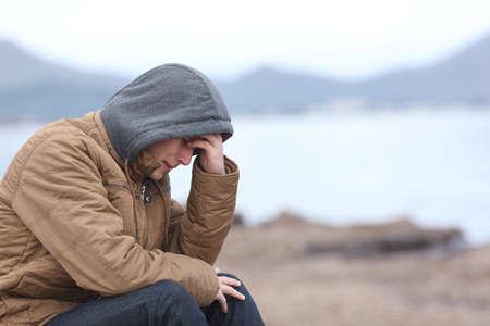 Bezorgd tiener man huilend op het strand in de winter in een slecht weer dag