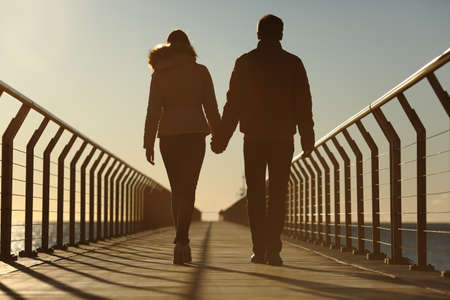 Back silhouette of a couple walking holding hands on a bridge in the beach at sunset