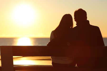 ハグとビーチで太陽を見ているカップルのシルエットの背面図