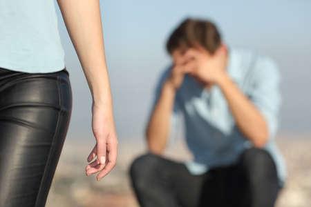 Breakup d'un couple avec un homme triste dans le fond et la petite amie lui laissant au premier plan Banque d'images - 37920142