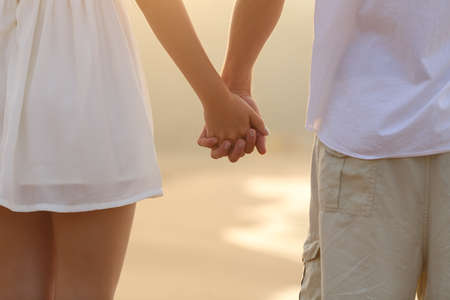 love at first sight: Close up of a back view of a couple walking and holding hands on the beach at sunrise Stock Photo