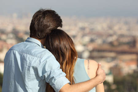 Back view of a couple dating in love hugging and looking the city in a sunny day 스톡 콘텐츠