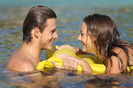 couple talking: Couple in summer vacation bathing in the water of the beach and looking each other Stock Photo