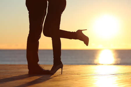 romantic couples: Couple legs silhouette hugging in love on the beach with the sun in the background at sunset